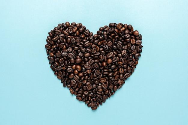 Grains de café en forme de coeur sur bleu.
