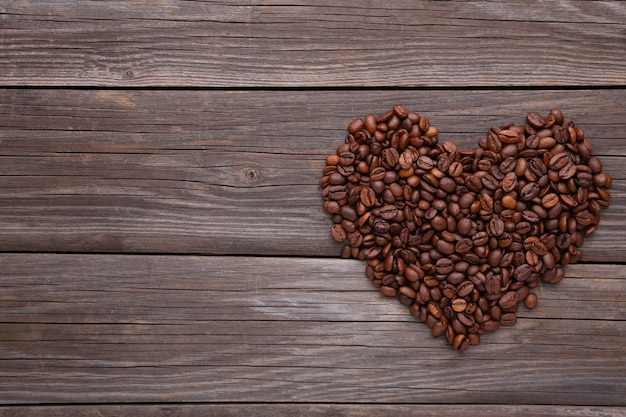 Grains de café en forme de coeur sur fond gris