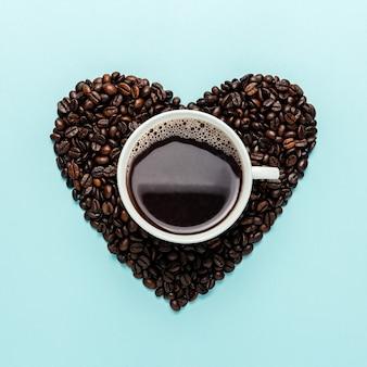 Grains de café en forme de coeur avec tasse blanche sur bleu.