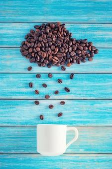 Grains de café en forme de nuage pluvieux avec une tasse sur fond bleu. concept météo