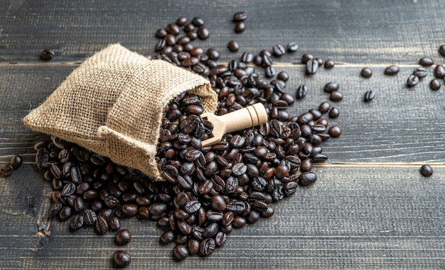 Grains de café frais closeup dans le sac en toile de jute sur une surface en bois.