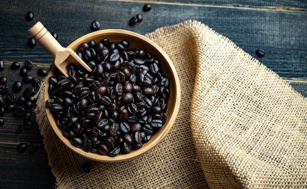 Grains de café frais dans un bol en bois sur un sac en toile de jute sur une surface en bois.