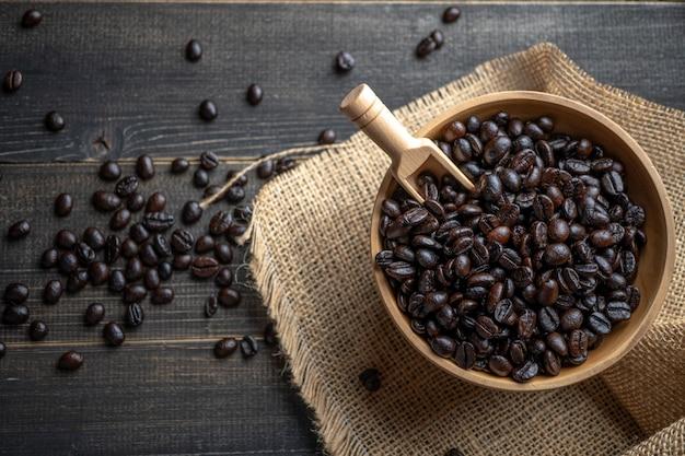 Grains de café frais dans un bol en bois sur un sac