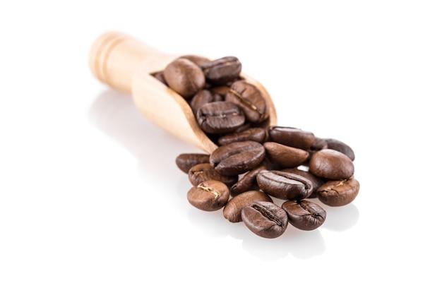 Grains de café frais dans une cuillère en bois isolé