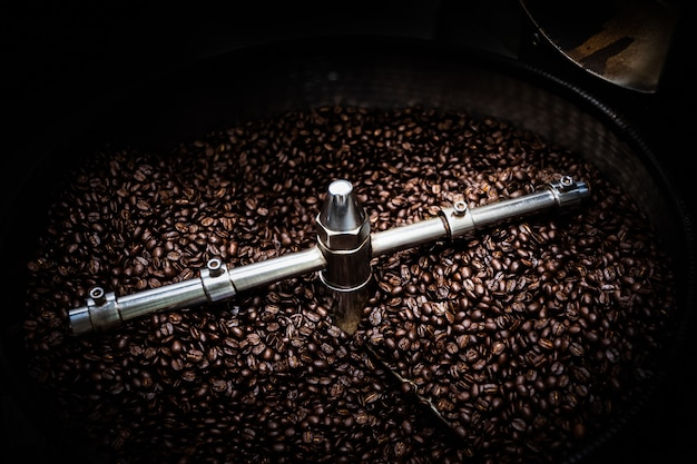 Des grains de café frais et une machine professionnelle de couverture de filature rôtie se bouchent concept de mouvement photo flou et fond sombre longue exposition