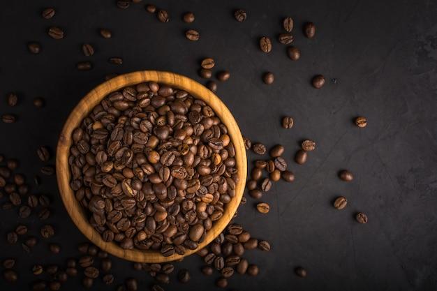 Grains de café frais torréfiés dans un bol en bois sur pierre noire