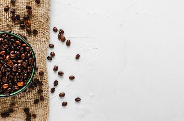 Grains de café frais et torréfiés dans une tasse sur toile de jute