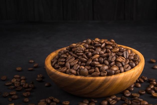 Grains de café frits dans un bol en bois sur pierre noire