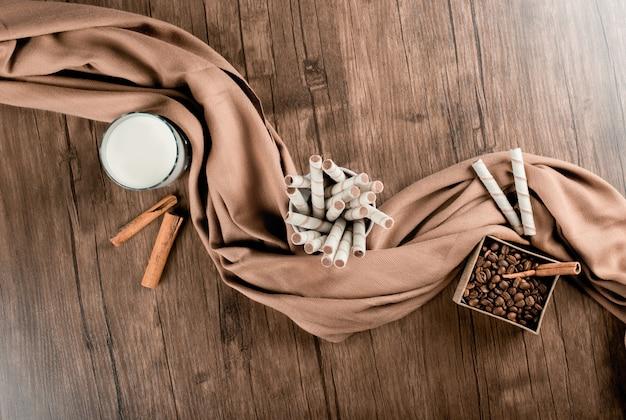 Grains de café, gaufres et un verre de lait enveloppé d'un foulard