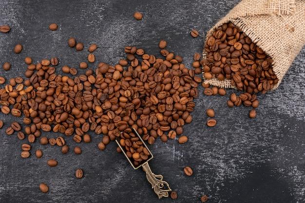 Grains de café en grains dans une cuillère en métal et un sac sur une surface sombre