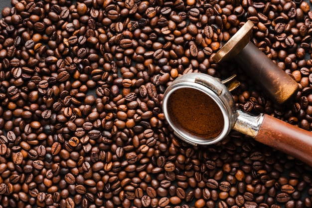 Grains de café gros plan avec bourreur