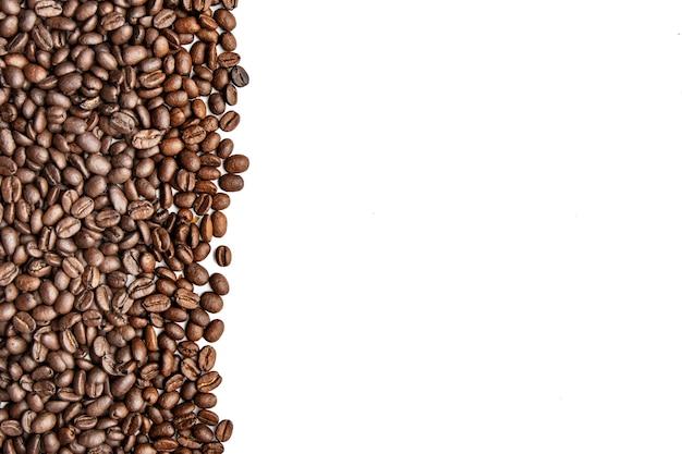 Grains de café isolés sur fond blanc. vue de dessus. copier l'espace pour le texte. fond de grains de café torréfiés