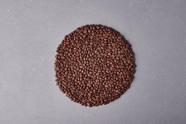 Grains de café isolés sur fond bleu.