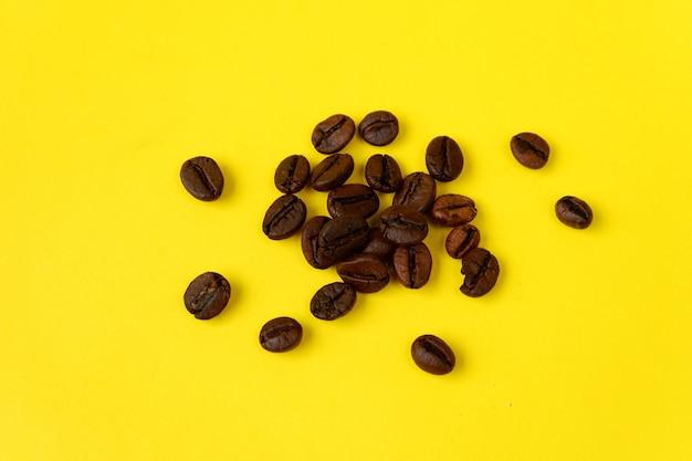 Grains de café isolés sur fond jaune