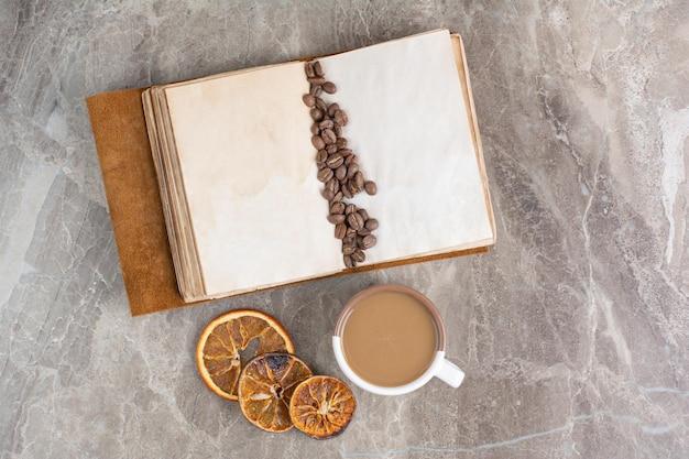 Grains de café sur livre avec tasse de café et tranches d'orange. photo de haute qualité