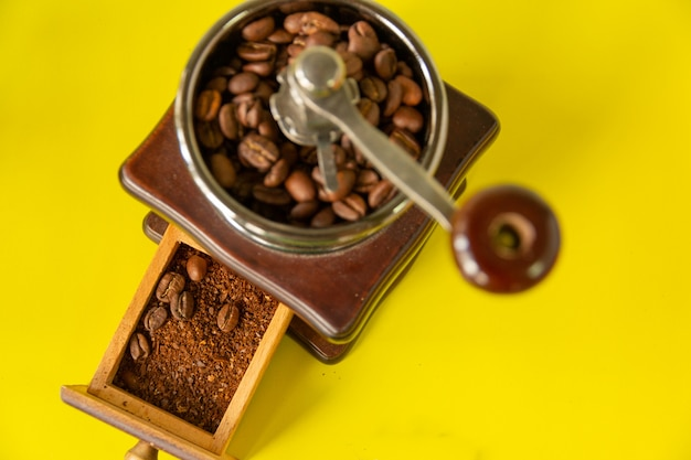 Grains de café de mise au point sélective et moudre le grain de café dans un moulin à café en bois vintage.