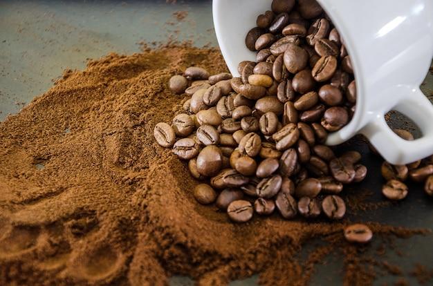 Grains de café et moulus dans une tasse blanche.