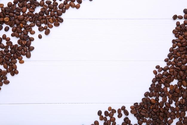 Grains de café naturels sur bois blanc