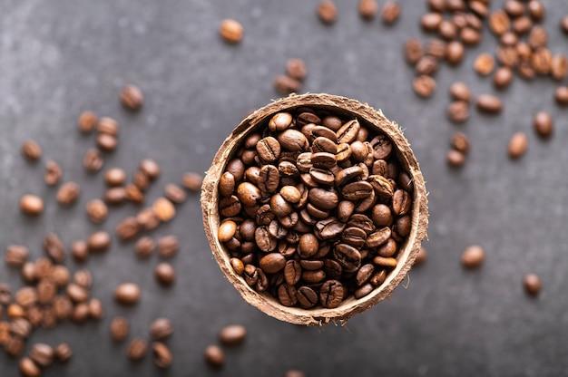 Grains de café noir arabica, aromatiques dans un plat de noix de coco sur fond de marbre foncé