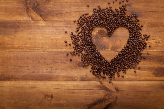 Grains de café noir en forme de coeur sur une table en bois marron, mise à plat