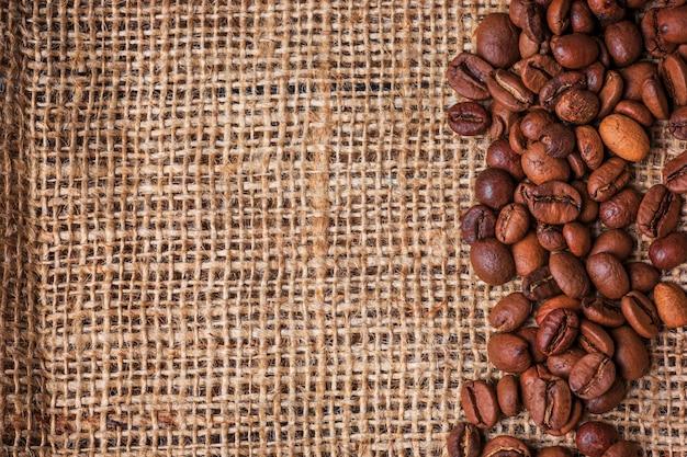 Grains de café noir en sac de jute sur table en bois,