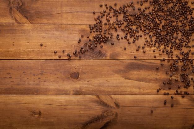 Grains de café noir sur une table en bois marron, vue de dessus, mise à plat, espace copie