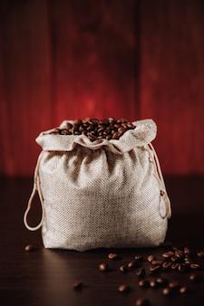 Grains de café noirs en sac.