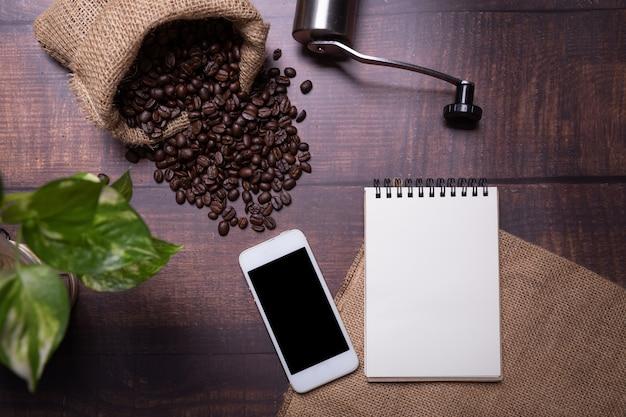 Grains de café avec note smartphone et papier.