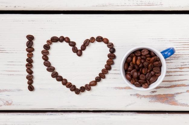 Grains de café organisés en forme de coeur. tasse blanche remplie de tas de grains de café crus. bois blanc en surface.