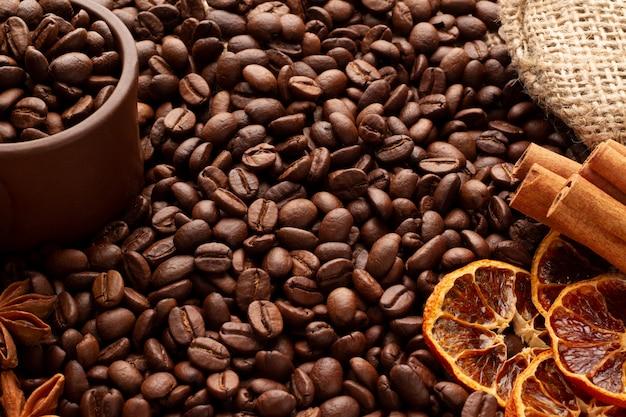 Les grains de café parfumés arabica et robusta sont dispersés sur un sac. tasse d'argile grains de café cannelle