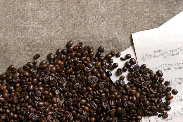 Grains de café et partitions sur fond de toile de jute