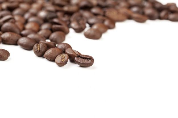 Grains de café pilé isolés sur blanc