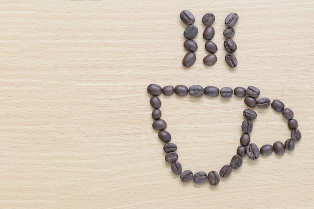 Grains de café placés en forme de tasse à café sur le fond de bois.