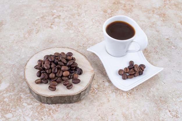Grains de café sur une planche de bois et un plateau à côté d'une tasse de café infusé
