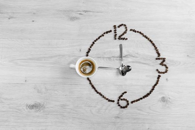 Grains de café pliés sous la forme d'une horloge. au lieu du numéro 9, une tasse de café, ce qui signifie qu'il est temps de boire du café