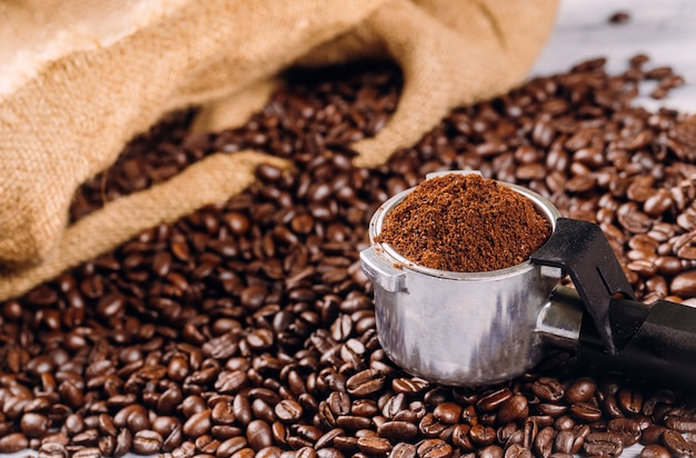 Grains de café et porte-filtre avec du café moulu torréfié
