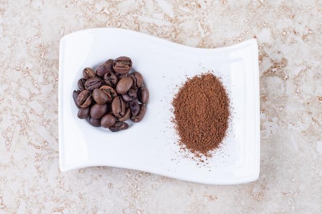 Grains de café et poudre de café moulu sur un plateau de fantaisie