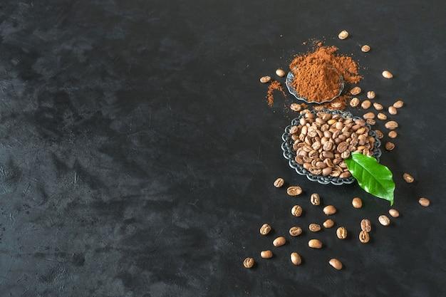 Grains de café et poudre moulue sur tableau noir. vue de dessus avec espace copie.
