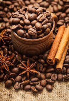 Grains de café renversés dans une tasse faite main d'argile avec de la cannelle et de l'anis