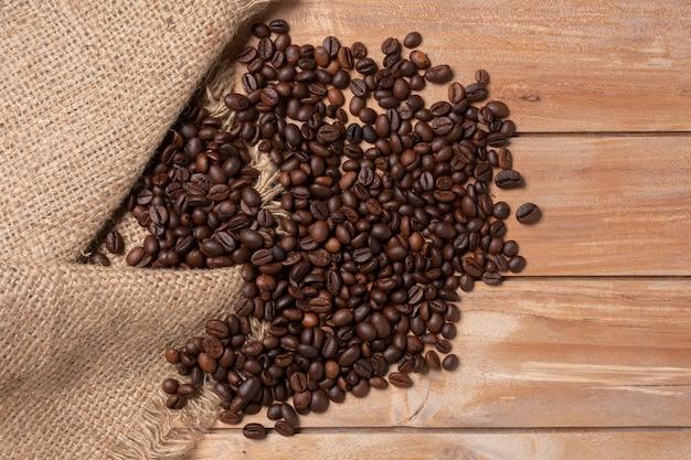 Grains de café robusta sur le fond de la table en bois