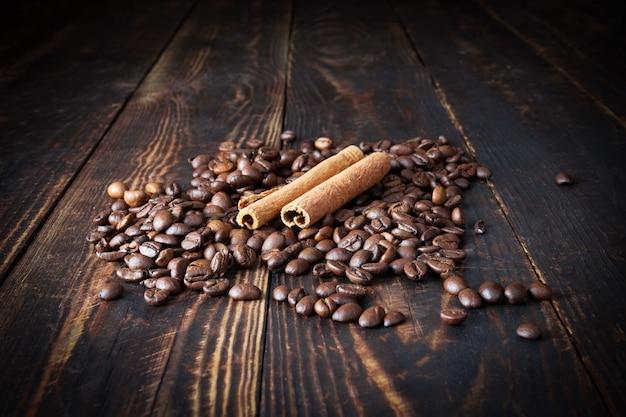 Grains de café saupoudrés et deux bâtons de cannelle sur une surface en bois de planche brune