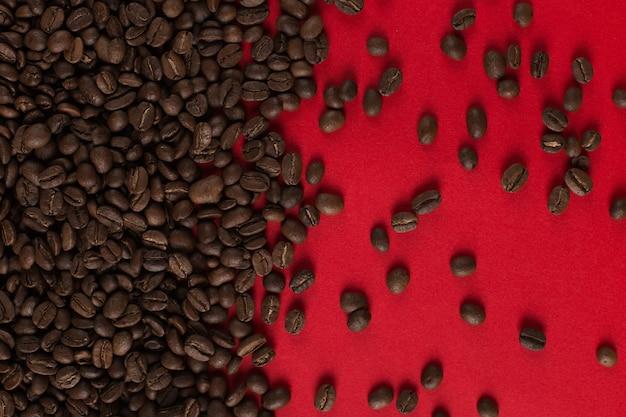 Les grains de café sont dispersés sur un fond de papier rouge, une surface commerciale.