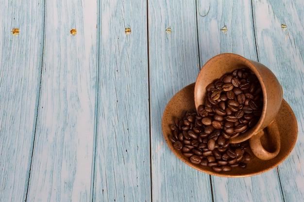 Les grains de café sont dispersés d'une tasse inversée sur une soucoupela tasse est à droite contre une lumière