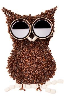 Les grains de café sont disposés sous forme de hibou assis sur une branche de cubes de sucre avec les yeux des tasses