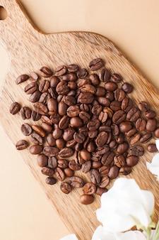 Les grains de café sont éparpillés sur une planche de bois sur un fond marron. photo verticale.