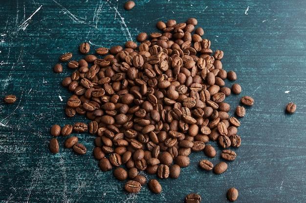 Grains de café sur une surface bleue.