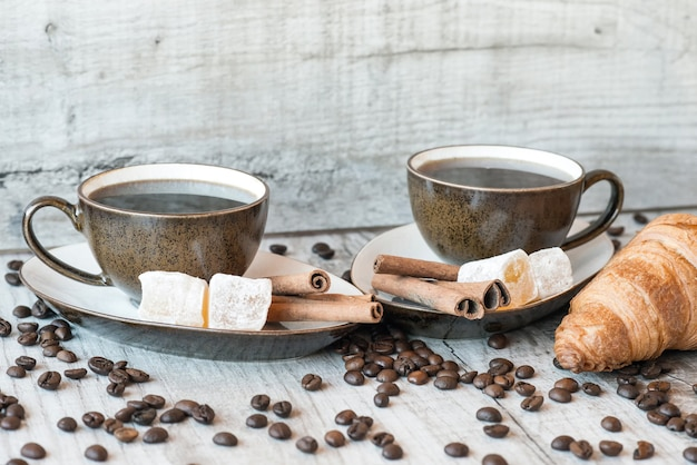 Grains de café sur table en bois avec des bonbons et des croissants
