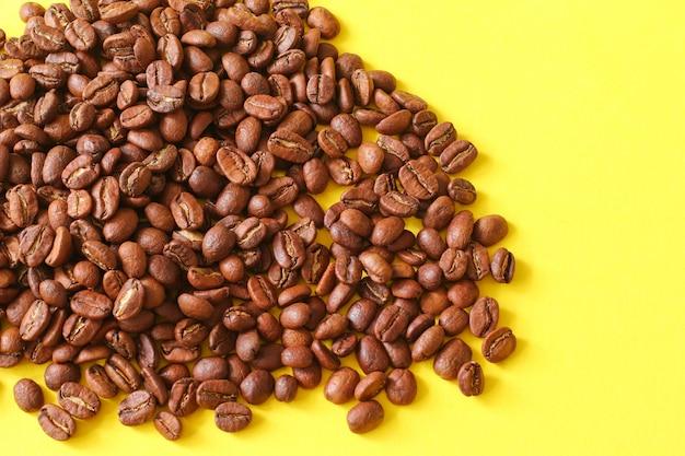 Grains de café en tant que fond isolé sur fond jaune.
