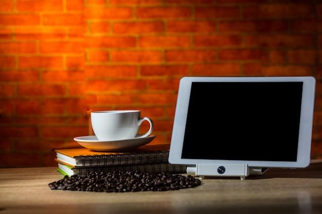 Grains de café avec une tasse blanche sur le livre et l'ipad
