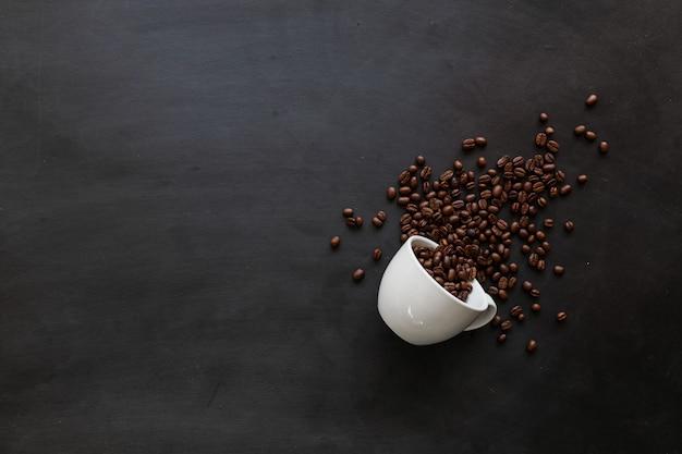 Grains de café et tasse blanche sur plancher en bois noir